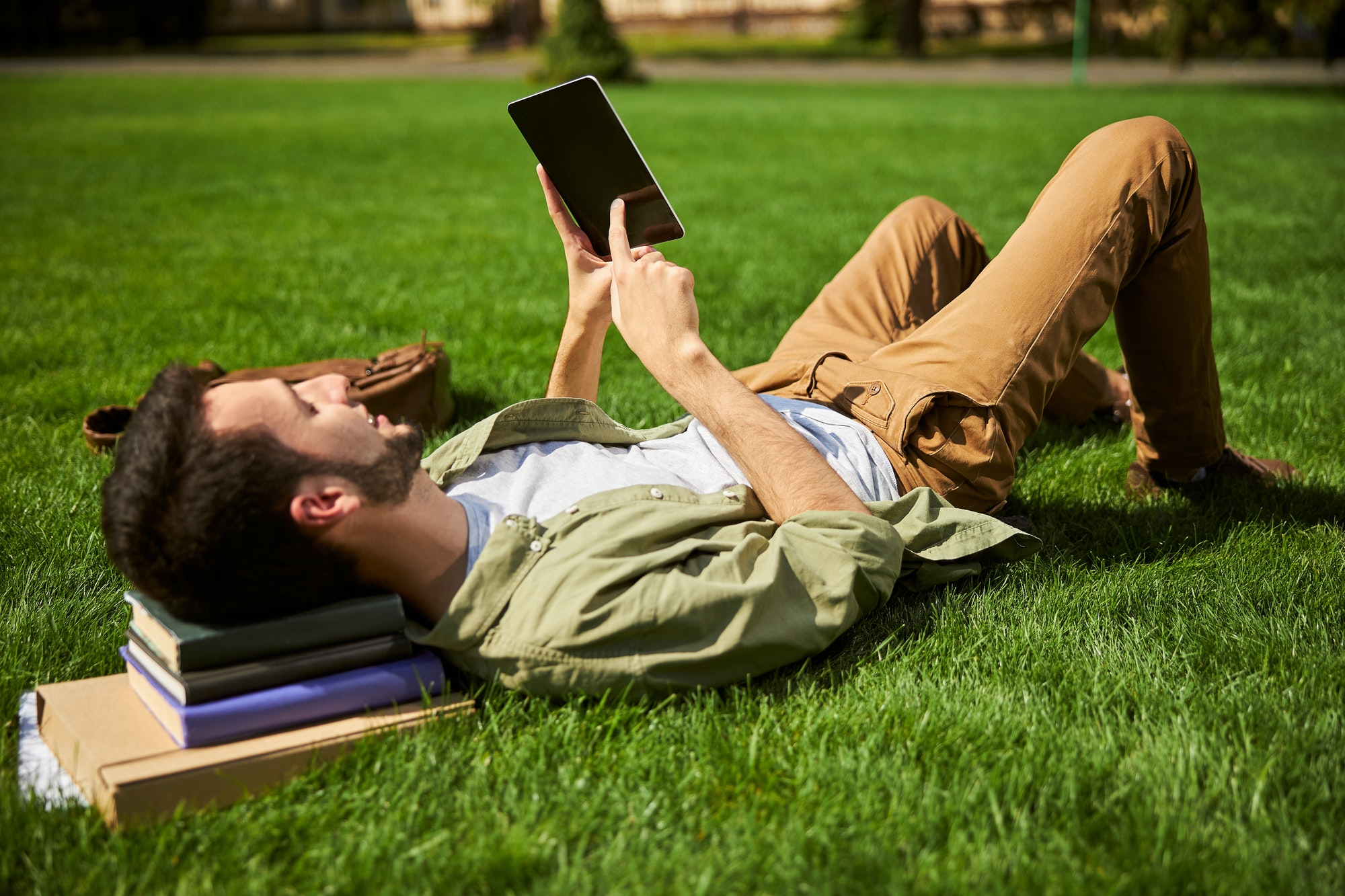 Smiling college student lying on the grass